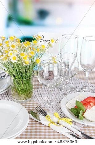 Table setting with chamomiles on checkered tablecloth on window background