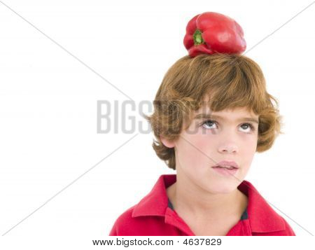 Young Boy With Red Pepper On His Head Frowning