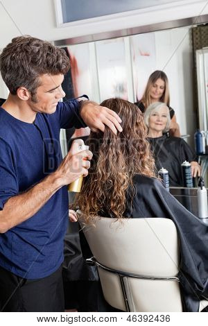 Hairstylists setting up female customer's hair at beauty parlor