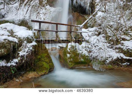 Bridge With Waterfall In Winter