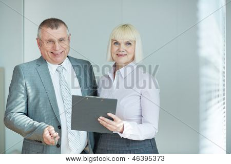 Confident mature co-workers looking at camera with smiles