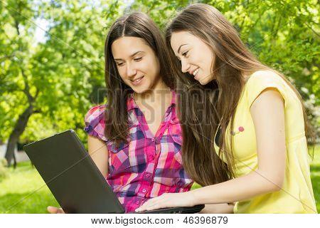 Smiling Female Students Using Laptop