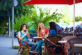Young Female Friends Sitting On Cafe Terrace, Urban Outdoors