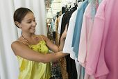 Smiling young woman looking through clothing rack in the store