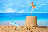stock photo of spade  - Sandcastle with windmill on summer beach - JPG