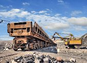 stock photo of iron ore  - Loading of iron ore on the train in career - JPG