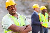 image of ppe  - smiling african mine worker at mining site with colleagues - JPG