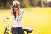 stock photo of outdoor  - smiling young woman using a camera to take photo outdoors at the park - JPG