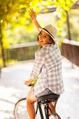cheerful young woman riding her bike waving goodbye