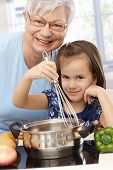 stock photo of granddaughter  - Grandmother and little granddaughter cooking at home - JPG