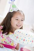 Young Girl Wearing Party Hat Looking At Birthday Cake Smiling