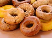 Closeup of a group of assorted bagels on a wood table top with burlap in the background. Bagels incl