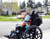 pic of biracial  - Happy disabled six year old boy waiting on sidewalk in wheelchair - JPG
