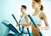 pic of training gym  - Portrait of pretty girl training on special sport equipment in gym - JPG