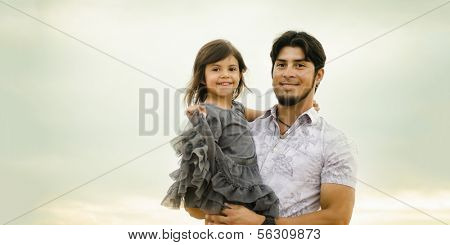 Happy smiling man holding his daughter who seems happy