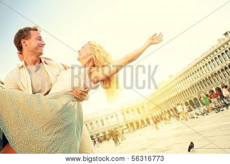 Romantic couple in love having fun embracing and laughing in Venice, Italy on Piazza, San Marco. Happy young couple on travel vacation on St Mark's Square. Man carrying woman in arms in sunset.