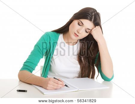 Young casual woman writing in workbook. Isolated on white.