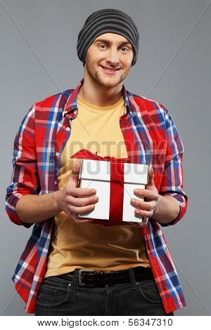 Stylish young man in shirt and beanie hat with gift box
