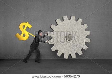 Businessman Rotating Large Concrete Gear With Money Winder On Back