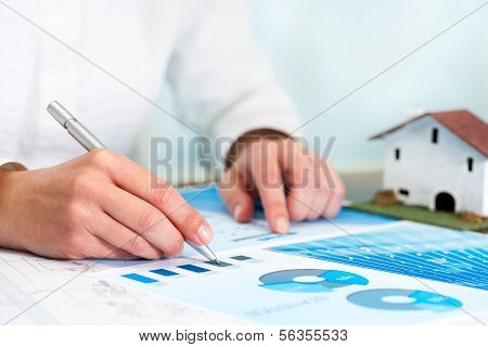 Female Hands Reviewing Stats.