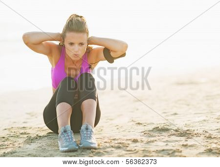 Healthy Young Woman Doing Abdominal Crunch On Beach