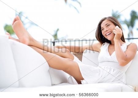 Smart phone - pretty woman mixed race asian caucasian talking on smart phone sitting relaxed on sofa smiling happy laughing having in white dress in couch relaxing with legs up at home.