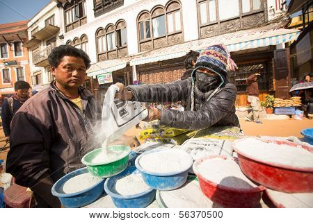 KHATMANDU, NEPAL - DEC 17: Unidentified man sell cement for donations for repairs near stupa Boudhanath during festive solemn Puja of Norbu Rinpoche's reincarnations, Dec 17, 2013 in Khatmandu, Nepal.