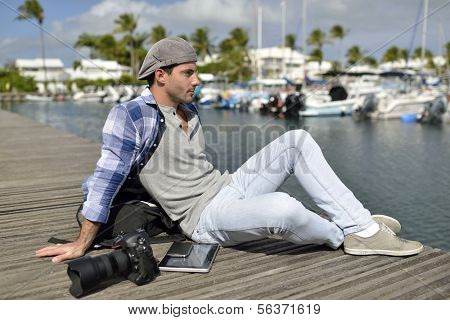 Photographer relaxing on marina wooden deck