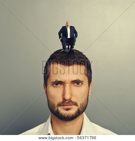 portrait of sad man with small man on the head
