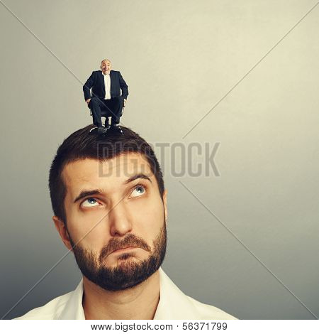 surprised man looking up at small man on the head