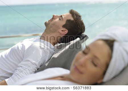 Couple relaxing in long chairs outside spa resort