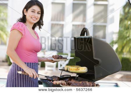 Cocinar en una parrilla de mujer