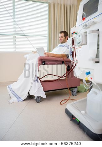 Male patient using digital tablet during renal dialysis treatment in hospital room