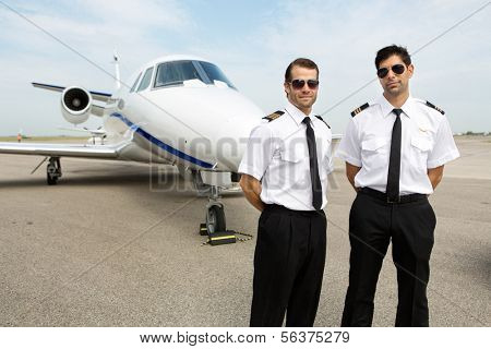 Portrait of confident pilots standing in front of private jet