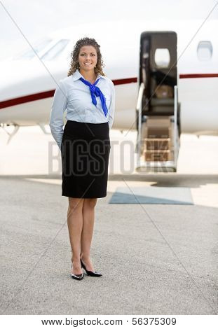 Full length of beautiful stewardess standing against private jet at terminal