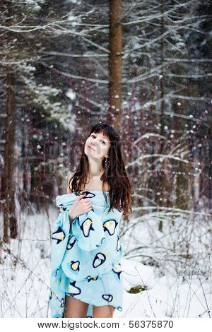 Beautiful woman under warm cute wrap in cold snow forest