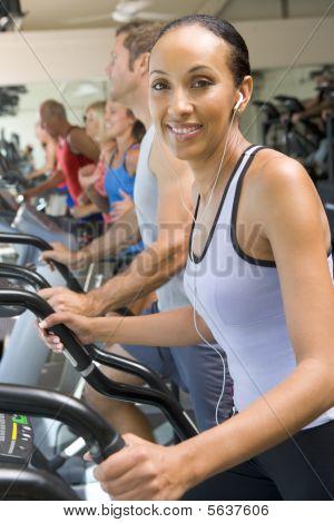 Mujer que corre en la cinta de correr en el gimnasio