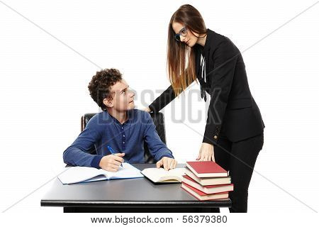 Teacher Standing Next To Student's Desk And Talking