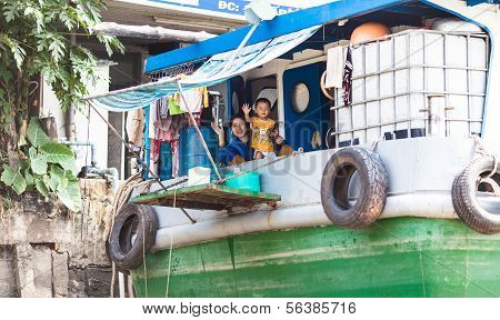Vietnamese woman and child waves to tourist in Mekong Delta