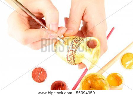 Hands paints on hand made ceramic amphora and art materials isolated on white