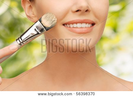 beauty amd make-up concept - closeup picture of beautiful woman with brush applying cream foundation
