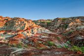 stock photo of dinosaur  - Near sunset over the Drumheller badlands at the Dinosaur Provincial Park in Alberta where rich deposits of fossils including dinosaur bones have been found - JPG