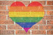 foto of transgendered  - Gay pride colored heart shape painted on old red brick wall - JPG