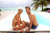 foto of infinity pool  - Couple sitting by infinity pool in tropical island - JPG