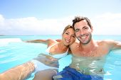 picture of infinity pool  - Cheerful couple swimming in infinity pool - JPG