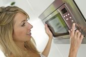 image of oven  - Woman at home using microwave oven - JPG