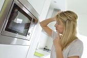stock photo of oven  - Woman at home using microwave oven - JPG
