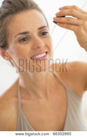 Portrait Of Young Woman Applying Cosmetic Elixir