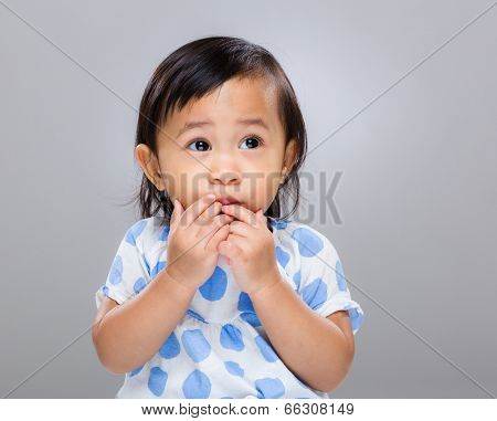 Little girl put finger into mouth