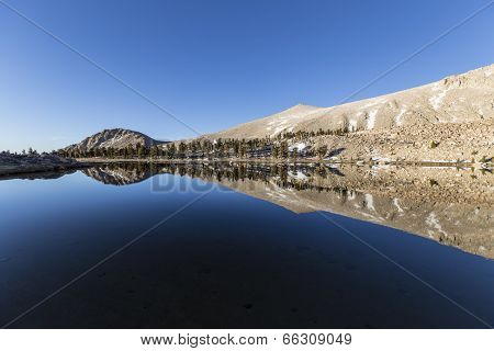 Calm water and mirror like reflection at Cirque lake high in California's Southern Sierra Nevada Mountain Range.